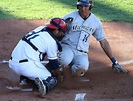 Whitecaps designated hitter Alexis Espinoza (14) slides in safely before the tag by Kernels catcher Carlos Ramirez (21) during the second inning of their game at Perfect Game Field at Veterans Memorial Stadium in Cedar Rapids on Wednesday, June 9, 2010. The Kernels defeated the Whitecaps 5-2.
