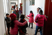 Students play in a corridor of the school complex in the remote settlement of Ngam-nak, Tibet (Qinghai, China). Ngam-nak serves as a school for Tibetan nomadic children, who are dropped off by their parents and spend 8 months a year in the remote settlement until they have completed a basic level of education. Staffed by a handful of teachers and cooks, there are no other activities in Ngam-nak apart from the school.