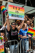 """New York, NY - 25 June 2017. New York City Heritage of Pride March filled Fifth Avenue for hours with groups from the LGBT community and it's supporters. A woman spectator holds a large sign reading """"Lez is more."""""""