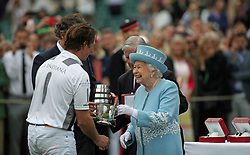 Queen Elizabeth II presents a trophy to La Inidiana's player Michael Bickford at the Cartier Trophy at the Guards Polo Club, Windsor Great Park, Surrey.