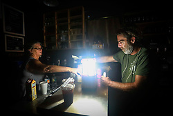 September 11, 2017 - Lake Worth, Florida, U.S. - KELLY OLIVE  (left) of Common Grounds Coffee Bar serves customer TED LEAL, of Lake Worth, by the light of a battery-powered lantern in the aftermath of Hurricane Irma Monday. ''We hope to have our generator up soon,'' she said. In the meantime, the coffee bar was offering pastries, banana bread, and cold brew coffee. (Credit Image: © Bruce R. Bennett/The Palm Beach Post via ZUMA Wire)