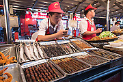Street vendor selling exotic foods at the night food market along Wangfujing Street shopping district in Beijing, China