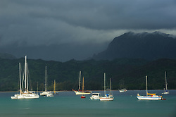 Anchored sailboats in Hanalei Bay rest against a backdrop of storm clouds over the island of Kauai near the north shore town of Hanalei in Hawaii.
