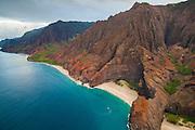 A tour boat is dwarfed by the fluted cliffs of the Na Pali Coast, Kauai, Hawaii.