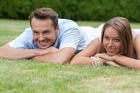 Smiling young couple lying on grass