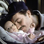 Hispanic American father bonding with 12 week old infant daughter. Fathers and children often form close bonds during the first year of life, this father engrossed with his infant daughter, is likely to go on to exert a strong influence on her social, emotional, and congnitive development