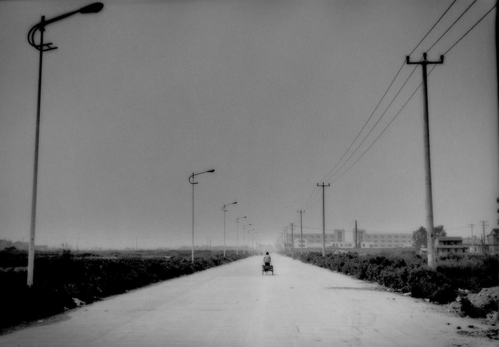 Woman peddles through a newly built road that runs through farmland soon to be converted to industrial estates, near Hongqiao Airport, Shanghai, China.