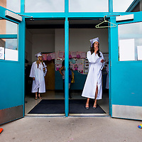 051513       Cable Hoover<br /> <br /> Amy Rosebrough, right and Aubrey Abweh peer out the doors of Roosevelt Elementary School as they and other Miyamura High School graduates line up for their graduation ceremony Wednesday at Public School Stadium.