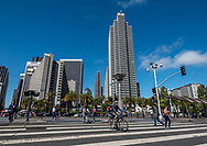 Wide pedestrian crossing with bicycles in front of Ferry Building with Embarcadero buildings in background. Street scene.