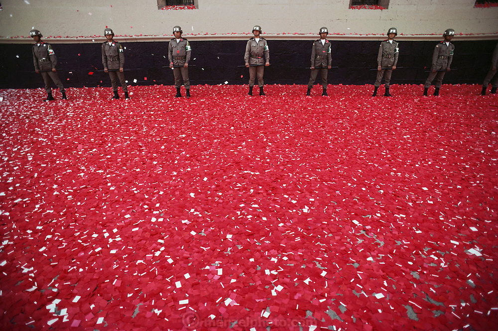 May 1, Worker's Day.  Troops in the Zocolo standing in red confetti and paper below where the president will speak in Mexico City, Mexico.
