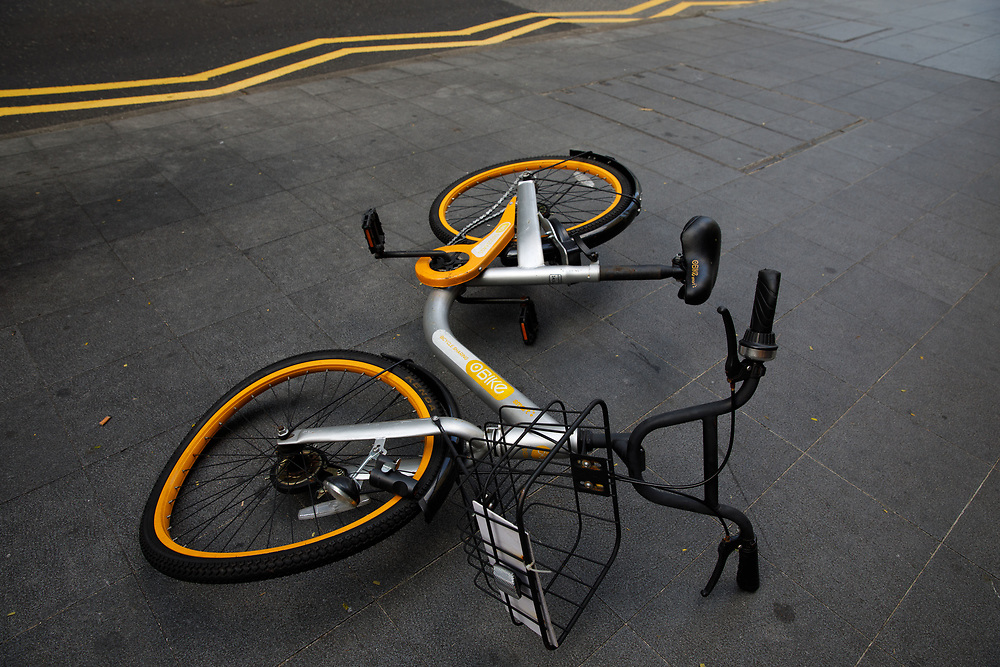 A damaged share bicycle rests on the footpath next to Orchard Road, Singapore.