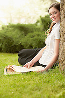 Woman sitting on grass holding newspaper side view portrait.