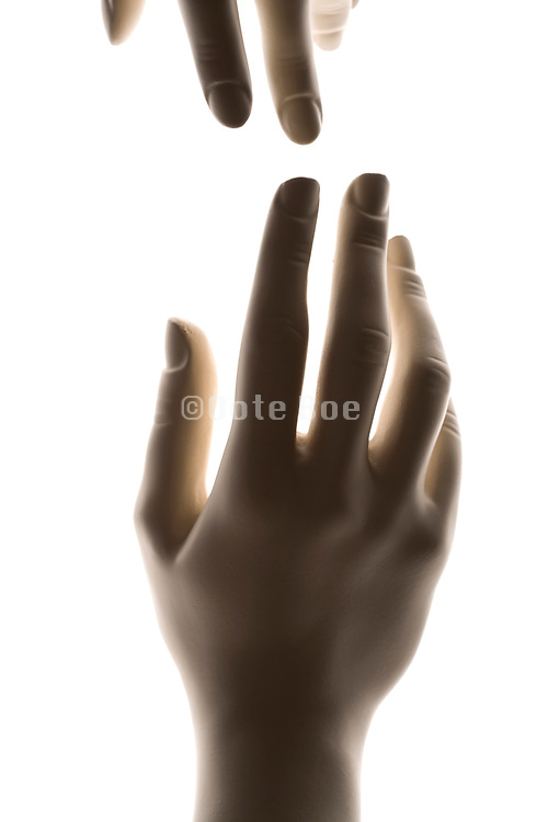 two mannequin hands almost touching