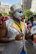 New York, NY - 25 June 2017. New York City Heritage of Pride March filled Fifth Avenue for hours with groups from the LGBT community and it's supporters. A marcher in thick white facepaint beats a drum.