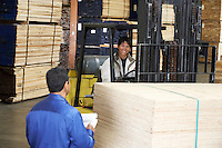 Workers with forklift carrying wood in warehouse