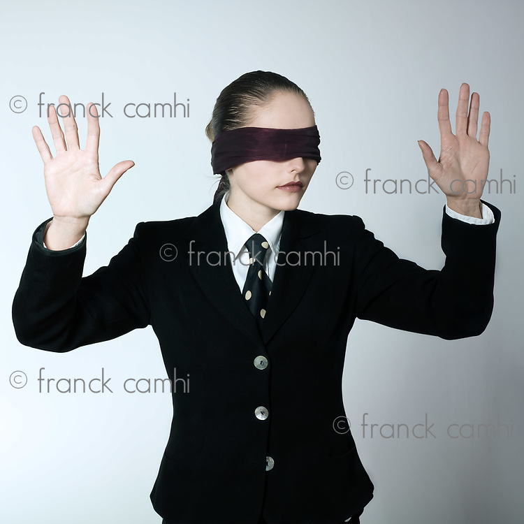 studio shot portrait of a beautiful young blindfold woman in a costume suit
