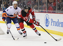 Mar 8; Newark, NJ, USA; New Jersey Devils right wing David Clarkson (23) skates with the puck while being defended by New York Islanders defenseman Mark Eaton (4) during the second period at the Prudential Center.