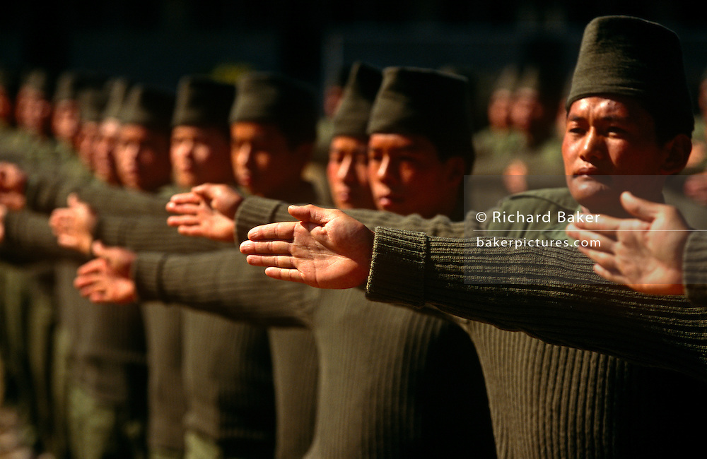 Young Nepali boys adjust their spacing during a camp parade after recruitment to the British Gurkha Regiment. The recruitment test for the Gurkha Regiment is part of a tough endurance series to find physically perfect specimens for British army infantry training. For example they will need to perform 25 straight-kneed sit-ups at a 45° slant both within 60 seconds to pass. 60,000 boys aged between 17-22 (or 25 for those educated enough to become clerks or communications specialists) report to designated recruiting stations in the hills each November, most living from altitudes ranging from 4,000-12,000 feet. After initial selection, 7,000 are accepted for further tests from which 700 are sent down here to Pokhara in the shadow of the Himalayas. Only 160 of the best boys succeed in the journey to the UK. The Gurkhas have been supplying youth for the British army since the Indian Mutiny of 1857.