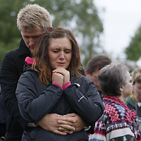 Members of Salem's Slavic community gather at the home on Fisher Road NE, on Wednesday, May 23, 2012, to bear silent witness for the four victims of a murder-suicide. A woman and three children were found in a burning house, and their cause of death was ruled as homicide. A man with connections to the family was found dead in his car, an apparent suicide, in Cottage Grove.