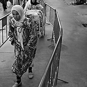 CEUTA, SPAIN - JUNE 27, 2010 : Moroccan women carrying goods on the passage of fences enabled in the warehouses next to the pedestrian cross border of Biutz.. Thousands  of people are involved in transporting smuggled goods from Ceuta (an Spanish enclave on the North African coast) to Morocco, it is estimated that every day enter 10.000 porters, mostly women, that it make between three and five trips to Morocco with all types of products purchased on  the warehouse border area of  Biutz in Ceuta, Spain.( Photo by Jordi Cami  )