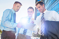 Mature businessman showing business plan on digital tablet with his colleagues