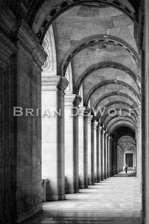 A woman walks through the long arched hallway adjacent to the Cour Napoleon of the Louvre.  Aspect Ratio 1w x 1.5h