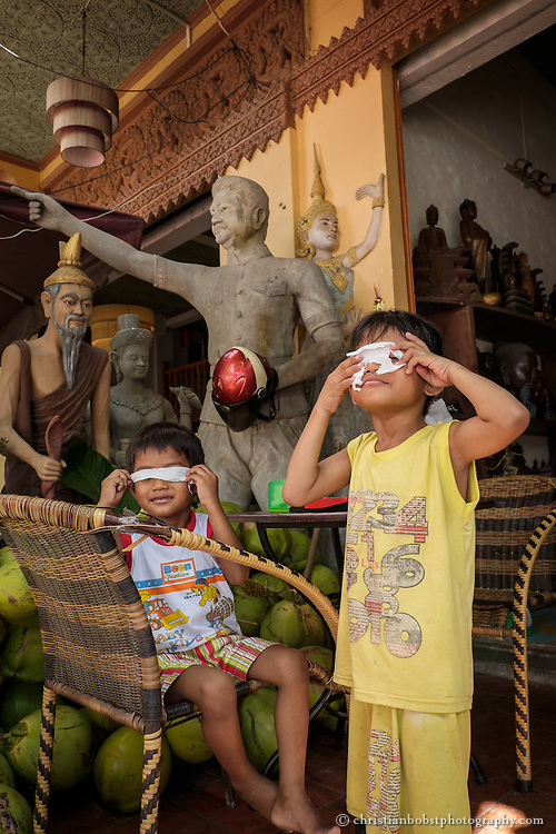Children play at the entrance of a souvenir- and sculpture shop near the royal palace.