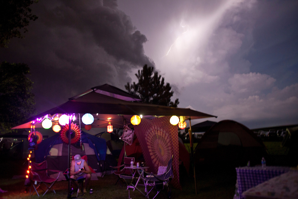 Adam Edwards of Rock Island checks his phone as a storm rolls in over Camp Euforia, north of Lone Tree, on Thursday, July 16, 2015. The storm halted the evening's outdoor performances, though campers and fest-goers continued their revelry late into the evening.
