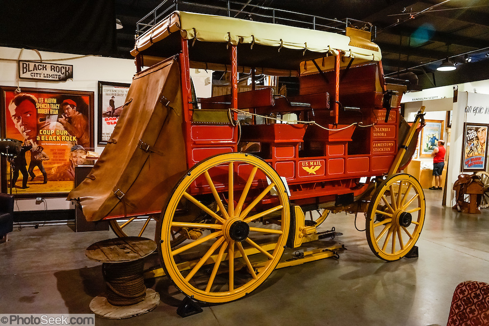 "This 3-seat, 9-passenger red Wells Fargo Express coach carried US Mail and passengers on rough roads in the West. This Celerity wagon was made by John Butterfield between 1858-1861 and much later converted with disc brakes for parade use. It was designed with half the weight of standard coaches and a lower floor for better shock absorption on rough, sandy, and steep trails. The name ""Celerity"" comes from the Latin root celer meaning swift. Celerity wagons covered 70 to 120 miles per day (averaging 4 to 7 miles per hour), making stops about every 20 miles. The Butterfield Overland Mail Trail was a stagecoach route operating from 1857 to 1861, carrying US mail starting from Memphis, Tennessee and St. Louis (Tipton), Missouri. The service routes converged at Fort Smith, Arkansas and passed through Indian Territory, New Mexico, and southern Arizona, ending in San Francisco. This particular wagon served the California towns of Stockton, Jamestown, Sonora, and Columbia. To discourage theft, gold and silver was not allowed on board; and the Butterfield Stage system was only attacked once, by Apaches. Fans of movies and television shouldn't miss the Museum of Western Film History, 701 S. Main Street, Lone Pine, California, 93545, USA. Web site: www.lonepinefilmhistorymuseum.org"
