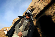 Sayed Mohammad Hussein, 22, is walking next to the entrance of the cave where he lives with his family since seven years, during a cold winter morning in Bamyan, central Afghanistan, an area mostly populated by Hazaras. A historically persecuted minority (15%) due to more lenient Islamic faith and characteristic 'Eastern' lineaments, Hazaras constitute the 70% of Bamyan's population.