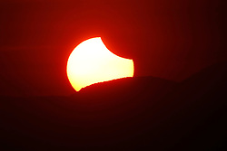 © Licensed to London News Pictures. 09/03/2016 Ipoh, Malaysia. A partial solar eclipse is seen, as the sun rises from behind the mountain, over the city of Ipoh in Malaysia, Wednesday, March 9, 2016. Photo credit : Sang Tan/LNP
