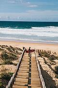 Surfer at Monte Clerigio beach, Western Algarve