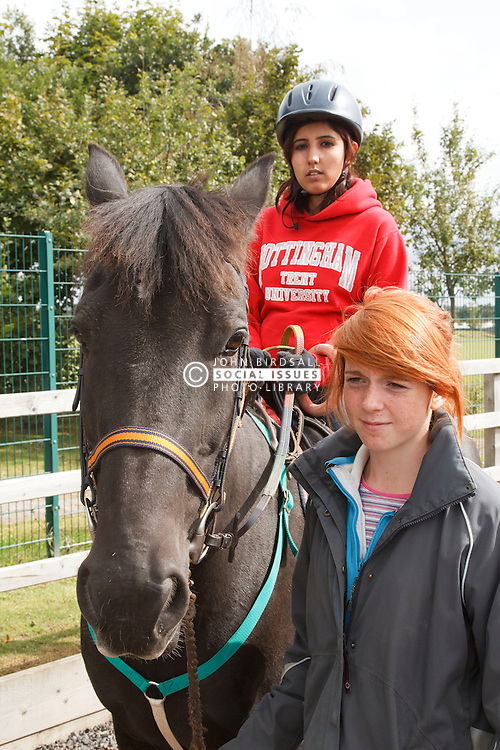 Woman with visual impairment  at riding lesson.