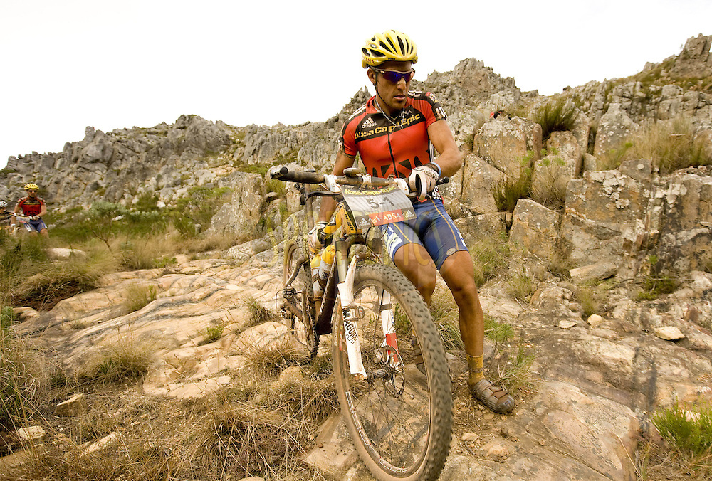 WESTERN CAPE, SOUTH AFRICA -  5 April 2008, Kevin Evans clambers over the old ox wagon pass at Gamtou Passduring stage eight of the 2008 Absa Cape Epic Mountain Bike stage race from Oak Valley, Elgin to Lourensford Estate, Somerset West in the Western Cape, South Africa..Photo by Karin Schermbrucker/SPORTZPICS