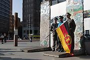 Un turista si fa fotografare con dei figuranti vestiti da ufficiali della DDR a Potsdamer platz  Berlino, Germania, 3 ottobre 2014. Guido Montani / OneShot<br /> <br /> A tourist poses for pictures with actors dressed as DDR officials at Potsdamer platz. Berlin, Germany, 3 october 2014. Guido Montani / OneShot