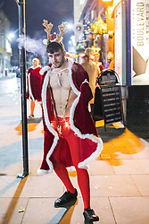 © Licensed to London News Pictures . 27/12/2016 . Wigan , UK . A man wearing a Christmas themed costume . Revellers in Wigan enjoy Boxing Day drinks and clubbing in Wigan Wallgate . In recent years a tradition has been established in which people go out wearing fancy-dress costumes on Boxing Day night . Photo credit : Joel Goodman/LNP