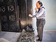 05 JUNE 2015 - KUALA LUMPUR, MALAYSIA:  A man prays in the front entrance to Sri Mahamariamman Temple, the oldest functioning and most important Hindu temple in Malaysia. The principal deity in the temple is Mariamman,  a deity that is popularly worshipped by overseas Indians, especially Tamils, because she is looked upon as their protector during the sojourn to foreign lands. Mariamman is a manifestation of the goddess Parvati, an incarnation embodying Mother Earth with all her terrifying force. She is associated with disease and fever and protects her devotees from unholy or demonic events.    PHOTO BY JACK KURTZ