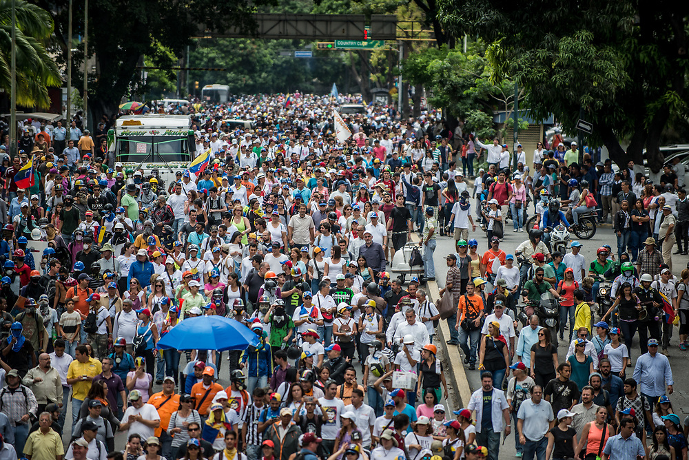 CARACAS, VENEZUELA - May 24, 2017: The streets of Caracas and other cities across Venezuela have been filled with tens of thousands of demonstrators for nearly 100 days of massive protests, held since April 1st. Protesters are enraged at the government for becoming an increasingly repressive, authoritarian regime that has delayed elections, used armed government loyalist to threaten dissidents, called for the Constitution to be re-written to favor them, jailed and tortured protesters and members of the political opposition, and whose corruption and failed economic policy has caused the current economic crisis that has led to widespread food and medicine shortages across the country.  Independent local media report nearly 100 people have been killed during protests and protest-related riots and looting.  The government currently only officially reports 75 deaths.  Over 2,000 people have been injured, and over 3,000 protesters have been detained by authorities.  PHOTO: Meridith Kohut