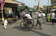 A hand drawn ricksha transporting its passenger