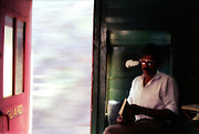 A guard looks at a book on the train from Kandy to Haputale in the hill country of Sri Lanka.