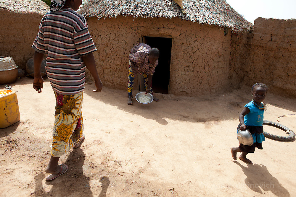 23 June 2010, Salogo, Burkina Faso. Female bricklayer, Asseta Ilboudo, was trained by local NGO, CREPA, to assist in building over 75000 latrines in rural Burkina Faso. In the rainy season when latrine building decreases, she sells her crops in the local market.