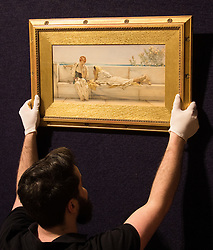 Bonhams, London, February 22nd 2017. Bonhams in London hold a press preview ahead of their 19th century paintings sale, featuring numerous valuable works including:<br /> • 'Children by the shore' by Dorothea Sharp, valued at £60,000-80,000<br /> • Barcas y pescaadores, Playa de Valencia by Joaquin Sorolla £60,000-80,000<br /> • When the Boats Come In by Walter Osborne valued at £100,000-150,000<br /> • A Solicitation by Lawrence Alma-Tadema which is expected to fetch between £30,000-50,000<br /> PICTURED: A Bonhams gallery porter hangs A Solicitation by Lawrence Alma-Tadema