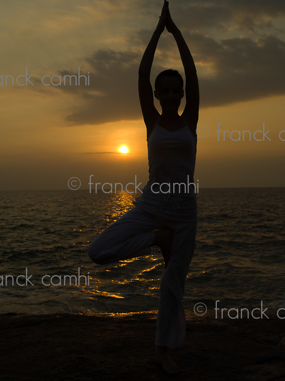 woman doing yoga tree pose by the seaside with sunset sunrise