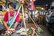 """26 SEPTEMBER 2012 - BANGKOK, THAILAND: A grilled banana vendor at work in Khlong Toey Market in Bangkok. Khlong Toey (also called Khlong Toei) Market is one of the largest """"wet markets"""" in Thailand. The market is located in the midst of one of Bangkok's largest slum areas and close to the city's original deep water port. Thousands of people live in the neighboring slum area. Thousands more shop in the sprawling market for fresh fruits and vegetables as well meat, fish and poultry.     PHOTO BY JACK KURTZ"""