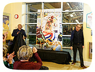 Garden City, New York, USA. March 9, 2019.  Audience applauds when, left of mural, DARIEN WARD the Baldwin Civic Association President, and at far right, MICHAEL WHITE the artist who painted mural of closeup of Nunley's Carousel horse, finish removing cover from mural during Unveiling Ceremony. Event was held at historic Nunley's Carousel in its Pavilion on Museum Row on Long Island.