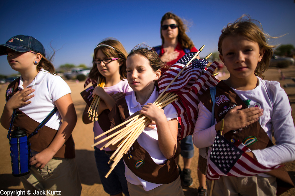 26 MAY 2012 - PHOENIX, AZ: Brownies from Troop 301 in Phoenix, AZ, salute during the National Anthem at the National Memorial Cemetery in Phoenix, AZ, Saturday. Hundreds of Boy and Girl Scouts along with the Young Marines, a Scout like organization, place American flags on veterans' graves in the National Memorial Cemetery in Phoenix every year on the Saturday before Memorial Day.  PHOTO BY JACK KURTZ