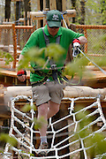 Chuck Fries, Park Manager at Bristol Mountain's new Aerial Adventure Park, crosses an obstacle on Tuesday, May 20, 2014. The park features six courses of varying difficulty, plus a children's course, and opens this weekend.