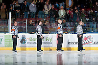 KELOWNA, CANADA - OCTOBER 20:  Matt Thurston, referee, Mike Langin, linesman, Jason Cramer, referee and Alex Teichroeb, linesman face the flag during the national anthem as the  Brandon Wheat Kings visit the Kelowna Rockets on October 20, 2012 at Prospera Place in Kelowna, British Columbia, Canada (Photo by Marissa Baecker/Shoot the Breeze) *** Local Caption ***