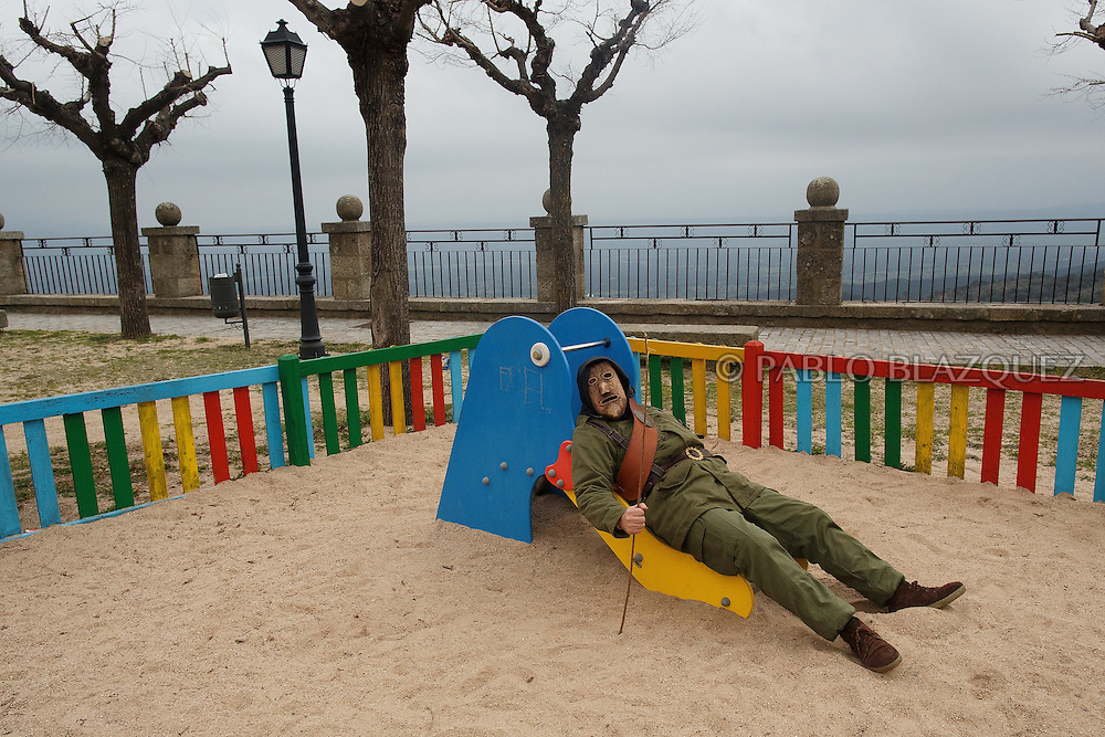 A Machurrero from Pedro Bernardo lies on a slide in a park during Carnival on February 6, 2016 in Pedro Bernardo, in Avila province, Spain. The origins of this pagan festival are unknown. The Machurreros wear wood masks, a military dress, black handkerchief, cowbells, and hold wicker stick. The festival disappeared after Dictator Franco forbid carnival festivals in 1937, but it was recently recovered. Before disappearing, male villagers after the military service, used to dress as Machurreros as they run along the streets scaring children and adults with their wicker stick to bring fertility to the land and expel the evil spirits. (© Pablo Blazquez)