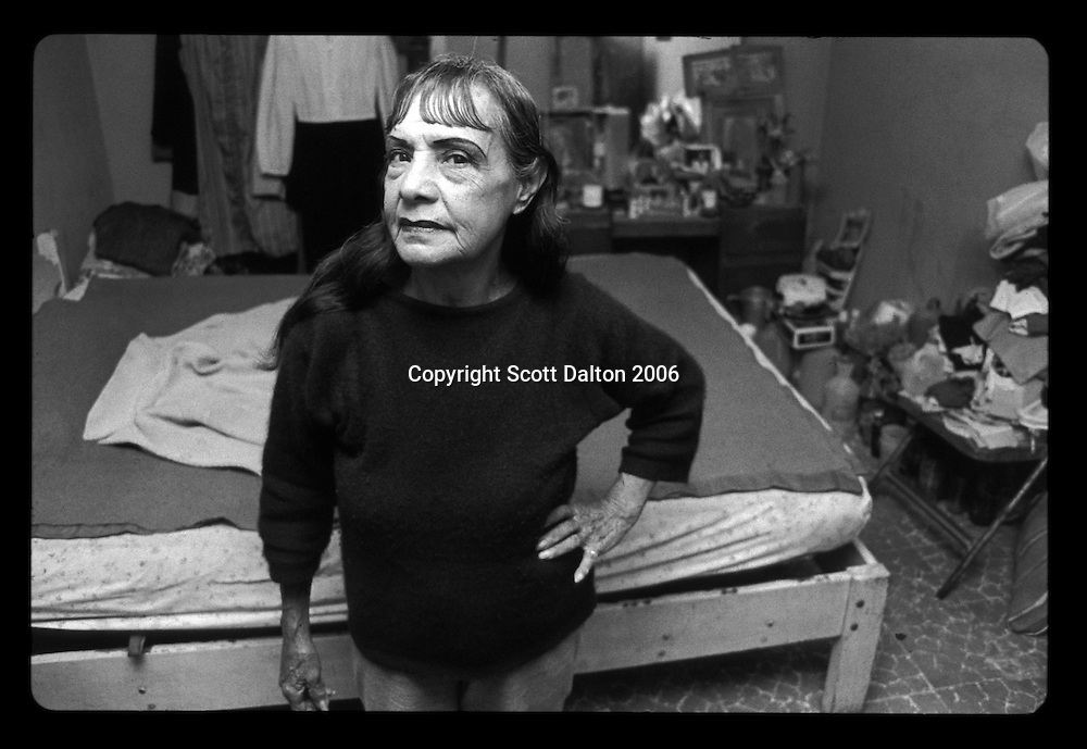 An elderly Prostitute waits for customers in her room in Boystown, in Nuevo Laredo Mexico, just across the US-Mexico border from Laredo, Texas. Boystown is a walled community, only one way in or out, which is home to the cities prostitution and red light bars. Many of the prostitutes who work there are transsexuals and transvestites. The idea behind the walled community is to isolate the activities associated with red light districts. (Photo/Scott Dalton)